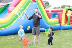 Man and two young boys playing with bubbles in front of inflatable slide