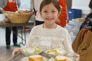 Photo of young girl holding tray of salads and bread