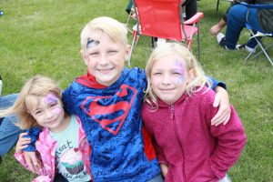 A young boy with his arms around two young girls with face paintings