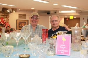 Two men in front of table of glasses and vases at a rummage sale