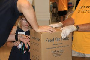 Two men and young girl packing up box of Food for Kidz