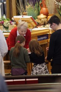 Two young girls receiving communion